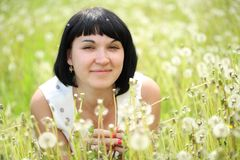 Young woman lying in the field of dandelion Royalty Free Stock Photography