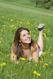 Young woman lying in a field with flowers Stock Image