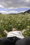Young woman lying on a field. Young woman relaxing lying on a field of flowers enjoying the nature - focus on the face Stock Images
