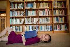 Young woman lying on floor in library Stock Image