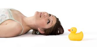 Young woman lying on floor looking at rubber duck Royalty Free Stock Photo