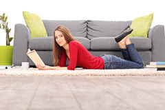 Young woman lying on the floor and reading a book Royalty Free Stock Image