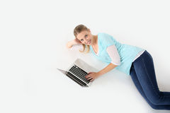 Young woman lying on floor using laptop Royalty Free Stock Photo