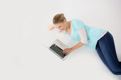 Young woman lying on floor using laptop Royalty Free Stock Photos