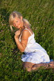 Young  woman lying in grass. Young blond woman in white dress lying in grass Stock Photo