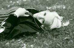 A young woman is lying in grass Stock Image