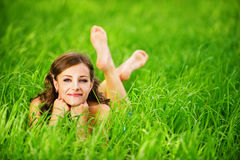 Young woman lying on grass. Portrait of young beautiful brunette woman lying on grass and propping up her face at summer green park Stock Image
