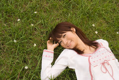 Young woman lying on grass. With smile Royalty Free Stock Photography