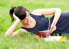 Young woman lying on grass with book Royalty Free Stock Photos