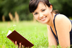 Young woman lying on grass with book Stock Photography