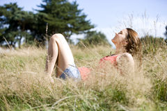 A young woman lying on the grass, enjoying the sunshine Stock Images