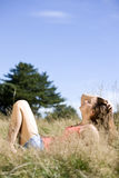 A young woman lying on the grass, enjoying the sunshine Stock Image