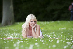 Young woman lying in a grass field wth daisies Stock Image