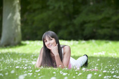 Young woman lying in a grass field wth daisies Stock Photo