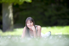 Young woman lying in grass field wth daisies Stock Photos