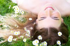 Young woman lying on grass with flowers in the park Royalty Free Stock Photos