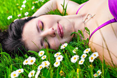 Young woman lying in grass with flowers royalty free stock images
