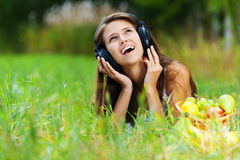 Young woman lying grass headphones Stock Photo