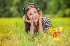 Young woman lying grass headphones fruit Stock Image