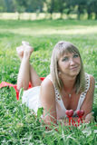 Young woman lying on the grass. In the park Stock Image