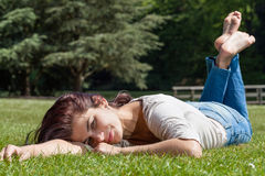 Young woman lying on grass. Young pretty brunette woman lying  on grass in a park Royalty Free Stock Images