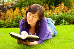 Young woman lying on the grass and reading a book Royalty Free Stock Image