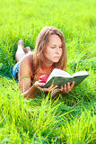 Young woman lying in grass reading book Stock Photography