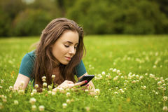 Young woman lying on the grass reading a message on a cell phone Stock Photo