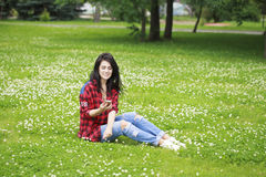 Young woman lying on the grass reading a message on a cell phone Stock Image