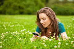Young woman lying on the grass reading a message on a cell phone Royalty Free Stock Image