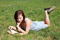 Young woman lying on grass, relaxing, reading book Royalty Free Stock Image