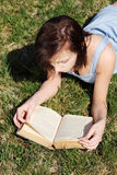 Young woman lying on grass, relaxing, reading book Royalty Free Stock Images
