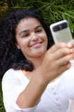 Young Woman Lying On Grass Sending Text Message Stock Images