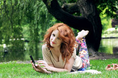 Young woman lying on grass. Smiling young woman playng with her mobile phone and relaxing at park Stock Images