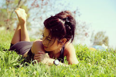 Young woman is lying in the grass Stock Photos