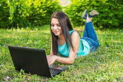 Young woman lying on the grass, using laptop and typing Royalty Free Stock Images