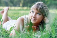Young woman lying on the grass. In the park Royalty Free Stock Images