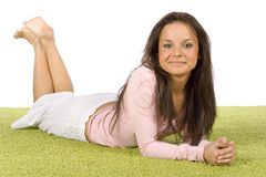 Young woman lying on the green carpet. Isolated on white young woman lying on the green carpet royalty free stock images