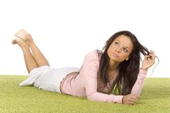 Young woman lying on the green carpet. Isolated on white young woman lying on the green carpet stock images