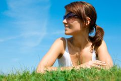 Young woman lying on the green grass Stock Image
