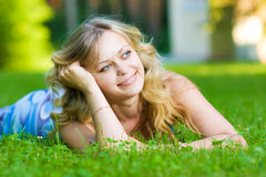 Young woman lying on a green grass Stock Images