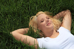 Young woman lying on green grass Royalty Free Stock Images