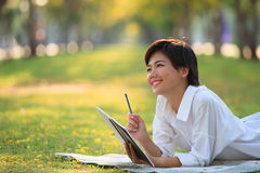 Young woman lying on green grass park with pencil and note book Stock Image