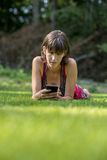 Young woman lying in green grass using her smart phone Royalty Free Stock Photo