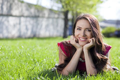 young woman lying on a green lawn Royalty Free Stock Photos