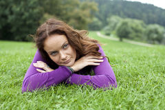 Young woman lying on a green lawn. Portrait of young woman lying on a green lawn royalty free stock photos