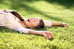 Young woman lying on a green lawn Royalty Free Stock Photography