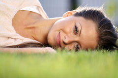 Young woman lying on a green lawn Stock Photography
