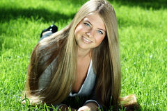 young woman lying on a green lawn Royalty Free Stock Image