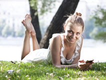 Young woman lying on a green lawn Royalty Free Stock Images